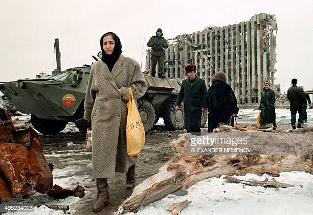 Chechen women and men pass in February 1996 by a Russian Army armoured personnel carrier in front of destroyed presidential palace in Grozny capital...