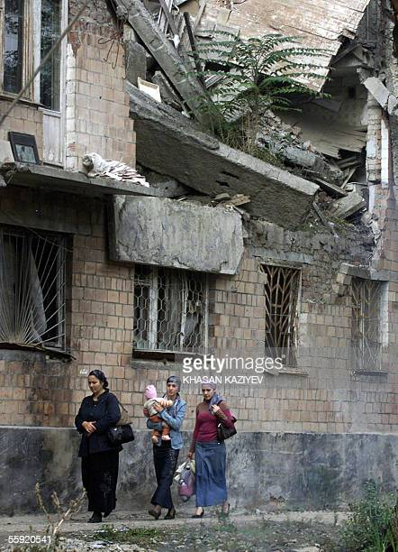 Chechen women pass by ruines of block of flats in the capital of Russia's wartorn republic of Chechnya Grozny 14 October 2005 Russian President...