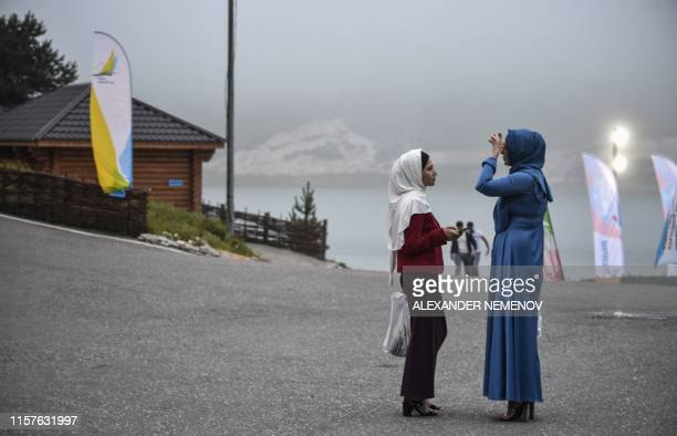Chechen women talk to each other at Kazenoy yachting club in Chechnya's Vedeno district on July 24, 2019.