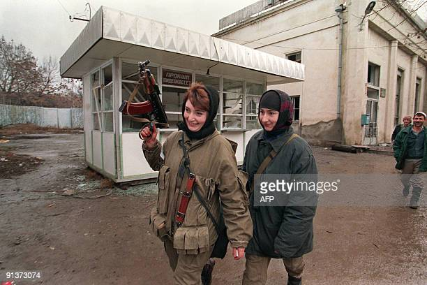Chechen women with an automatic weapon walk on January 12 1995 to the frontline in downtown Grozny