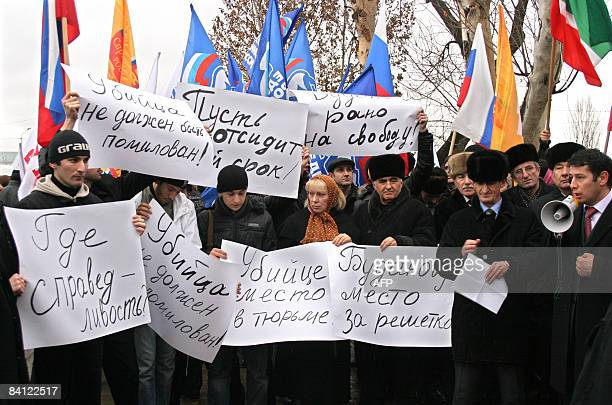 "Chechens hold posters reading ""Where is a justice?"" and ""A murderer should be in a prison!"" during a rally against former colonel Yuri Budanov..."
