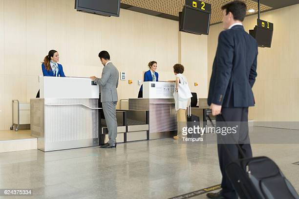 Check in counter stewardess and business traveler.