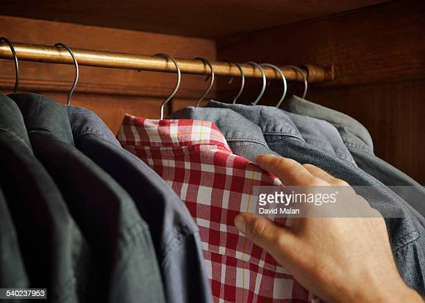 checked shirt being selected over grey shirts - one man only stock pictures, royalty-free photos & images