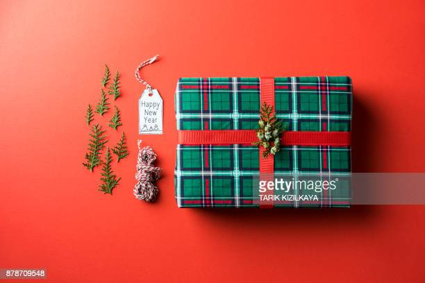 Checkered Christmas gift flat lay on red background