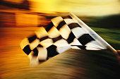 Checkered flag waving at an car race.