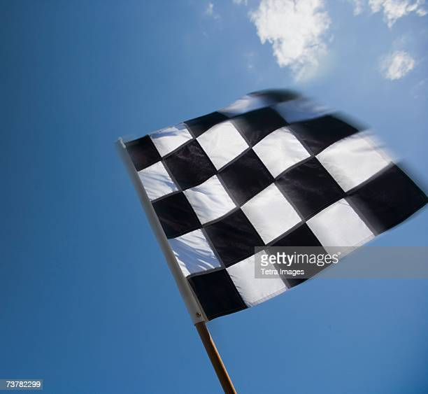 Checkered flag waving under blue sky