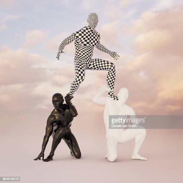 Checkered man balancing on shoulders of black and white men
