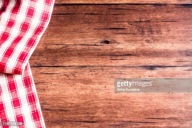 checkered red napkin on an old wooden brown background, top view. image with copy space. kitchen table with a towel - top view with copy space. - checked pattern stock pictures, royalty-free photos & images