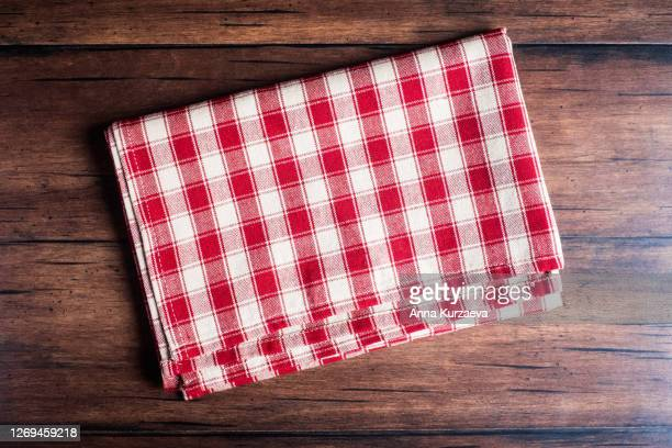 checkered red napkin on an old wooden brown background, top view. image with copy space. kitchen table with a towel - top view with copy space. - テーブルナプキン ストックフォトと画像