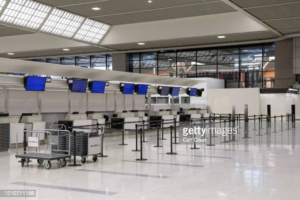 Check-in desks lie empty at Narita Airport on April 17, 2020 in Tokyo, Japan. Narita Airport, one of Japans busiest, has closed one of its 2 runways...