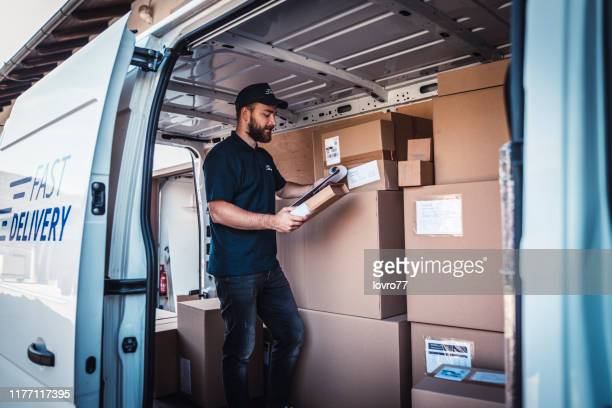 checking a list of packages - delivery person stock pictures, royalty-free photos & images