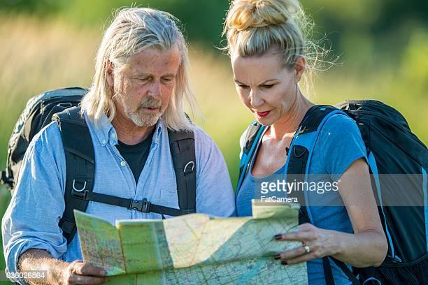 checking a map on a backpacking trip - irritatie stockfoto's en -beelden