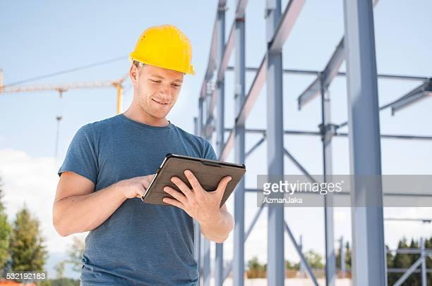Construcción revisando planes en tableta Digital