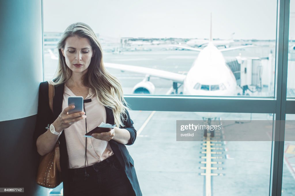 Checking her boarding schedule : Stock Photo