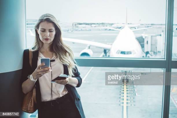 checking her boarding schedule - waiting stock pictures, royalty-free photos & images