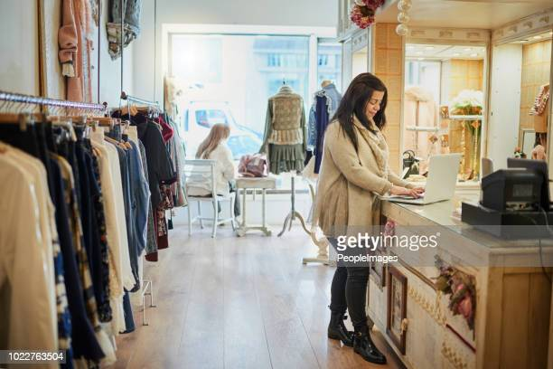 checking her online orders - happy merchant stock pictures, royalty-free photos & images