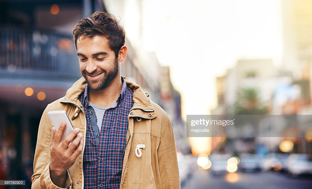 Checking his texts while in the city : Stock Photo