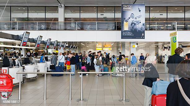 checking in at schiphol airport - schiphol airport stock photos and pictures