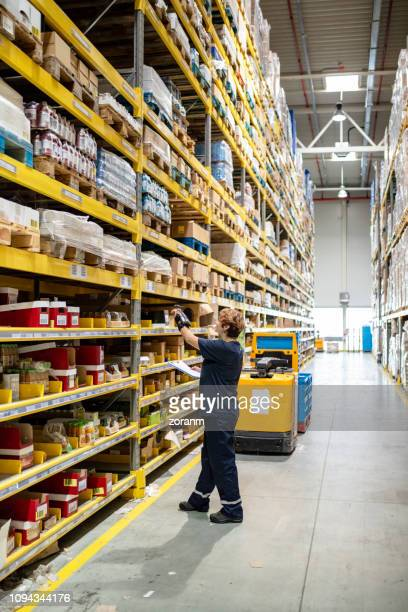 checking merchandise with wearable bar code reader - megastore stock photos and pictures