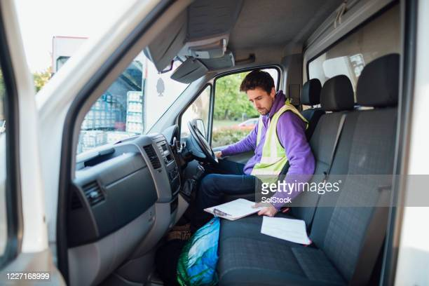 checking over delivery notes - one mid adult man only stock pictures, royalty-free photos & images