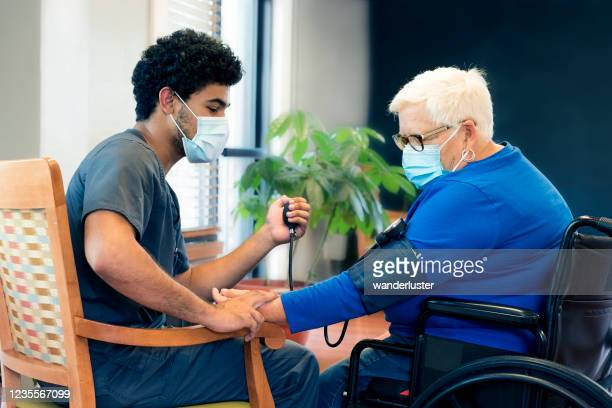 cna checking patient's blood pressure - frontline worker stock pictures, royalty-free photos & images