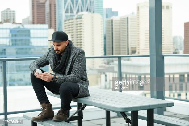 checking phone while waiting for someone - calgary alberta stock pictures, royalty-free photos & images