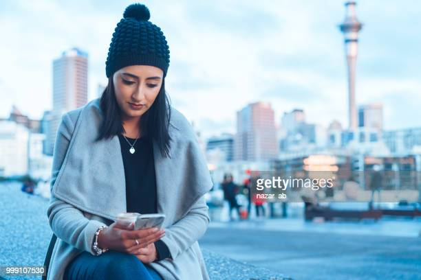 checking social media on phone with auckland city in background. - new zealand stock pictures, royalty-free photos & images