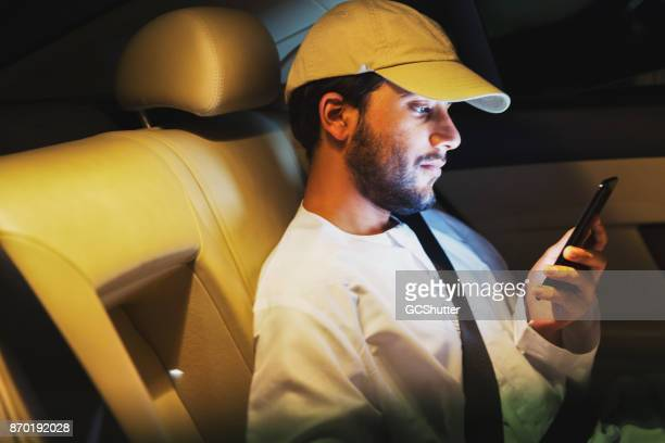checking some messages on the car ride home - candid forum stock pictures, royalty-free photos & images