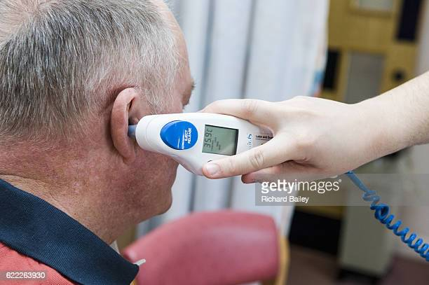 checking temperature in hospital with digital thermometer in ear. - digital thermometer ストックフォトと画像