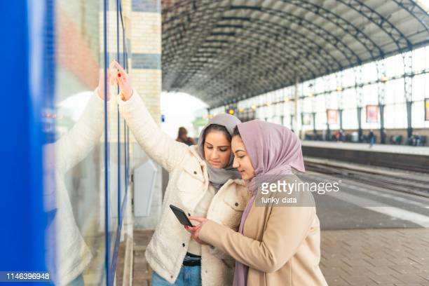 checking the departure time of train - north african ethnicity stock pictures, royalty-free photos & images