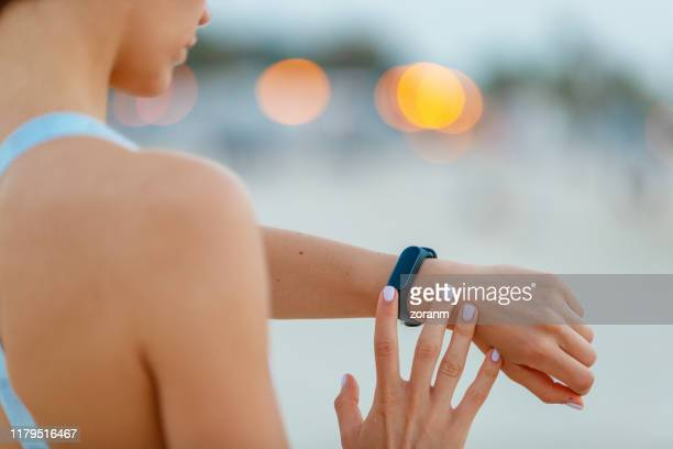 checking the fitness tracker on her wrist - fitness tracker stock pictures, royalty-free photos & images