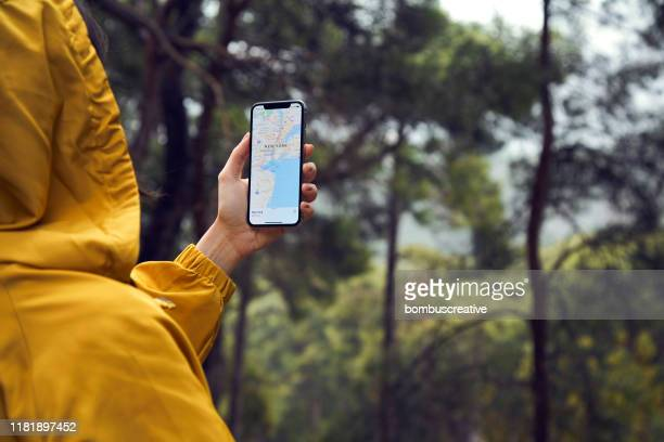 checking the map on iphone x in forrest - google stock pictures, royalty-free photos & images