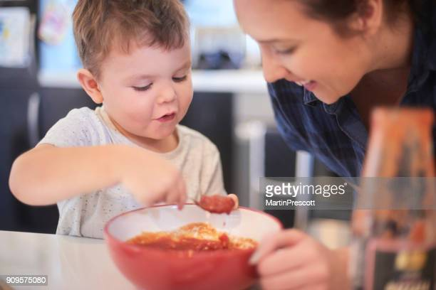 checking the pizza sauce with mummy - tomato sauce stock pictures, royalty-free photos & images