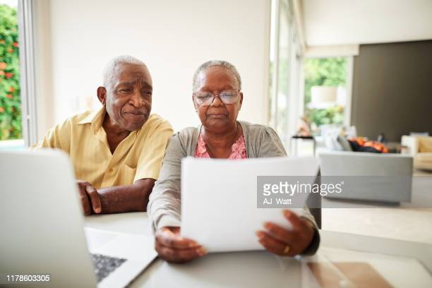 checking their monthly bills - bank statement stock pictures, royalty-free photos & images
