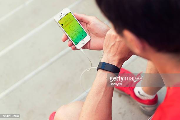 checking your fitbit-app in german - activiteit stockfoto's en -beelden