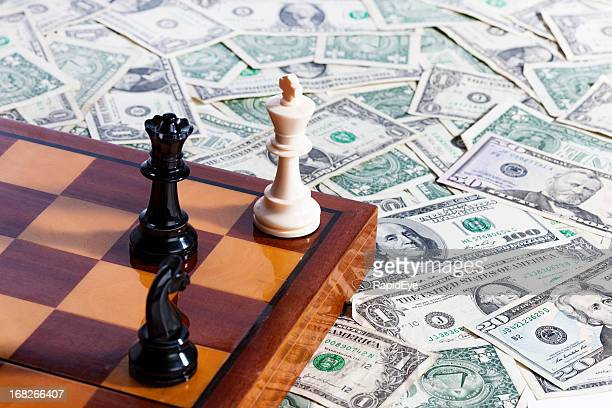 Checkmate! Chessmen and chessboard resting on pile of US currency