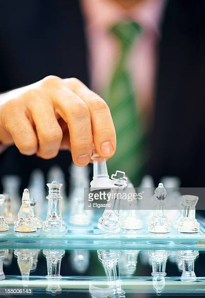 Checkmate - Hand holding chess piece by a king