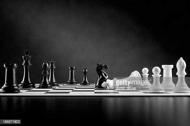 Checkmate move on chessboard, white king defeated, black and white