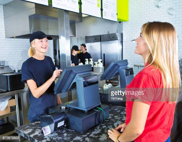 checkout server serving young woman customer ordering at fast food restaurant - pianale da cucina foto e immagini stock