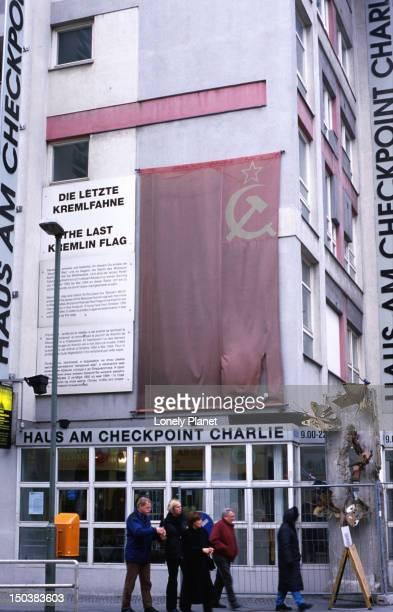 Checkpoint Charlie Museum covered by tattered Soviet flag on Friedrichstr, Kreuzberg.