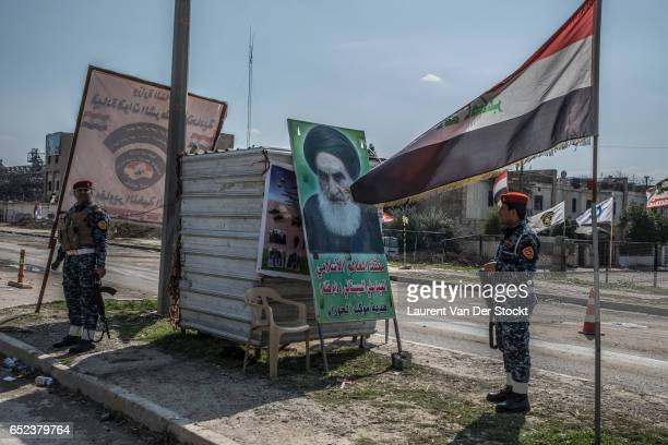 Checkpoint of the Federal Police at the entrance of western Mosul with an Iraqi flag and a portrait of the Ayatollah Sistani.