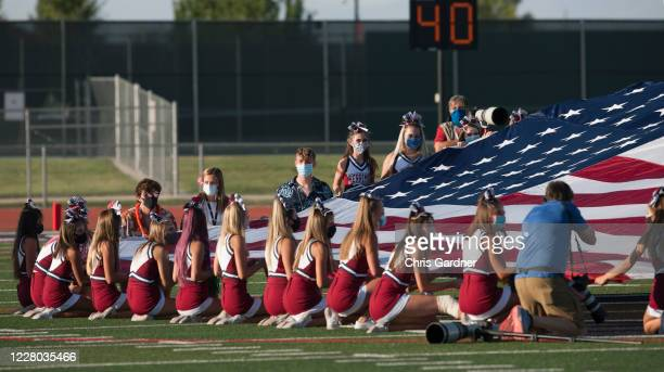 Cheer leaders of the Herriman Mustangs hold the American Flag during the National Anthem before their game against the Davis Darts at Mustang Stadium...