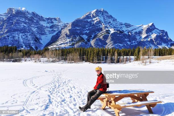 cheerful 66 years old caucasian senior adult  sitting on a bench  in the canadian rockies - kananaskis country stock pictures, royalty-free photos & images