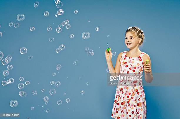 Cheerful, 9 years old girl blowing soap bubbles with fun