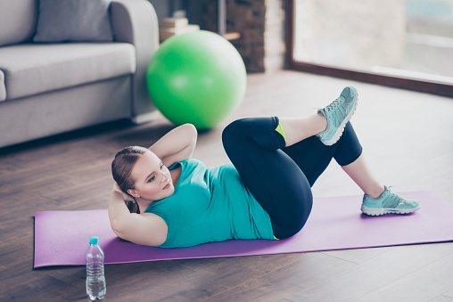 Cheerful active excited concentrated positive model fatty woman is improving muscles on her stomach, she is doing crunches on the floor at home 932365686