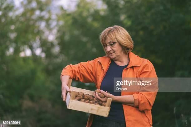 Femme Senior actif joyeuse avec caisse de noix