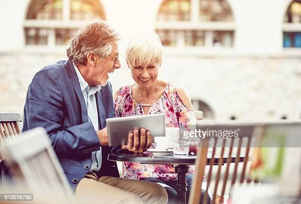 Joyeux adulte couple dans le café à l'aide de tablette numérique