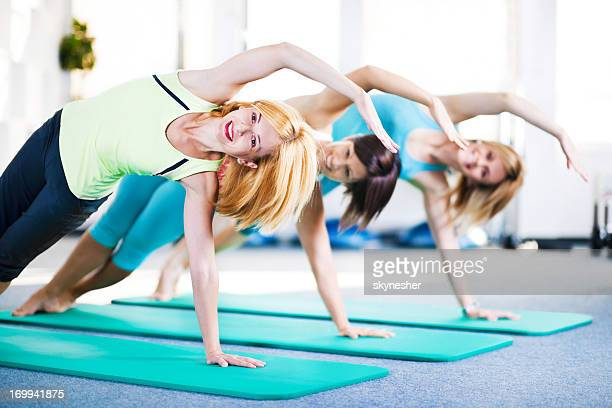 Cheerful adult women doing stretching exercises on Pilates class