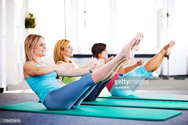 Cheerful adult women doing stretching exercises on Pilates class.