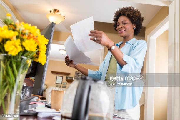 Cheerful African American businesswoman reviews documents in home office